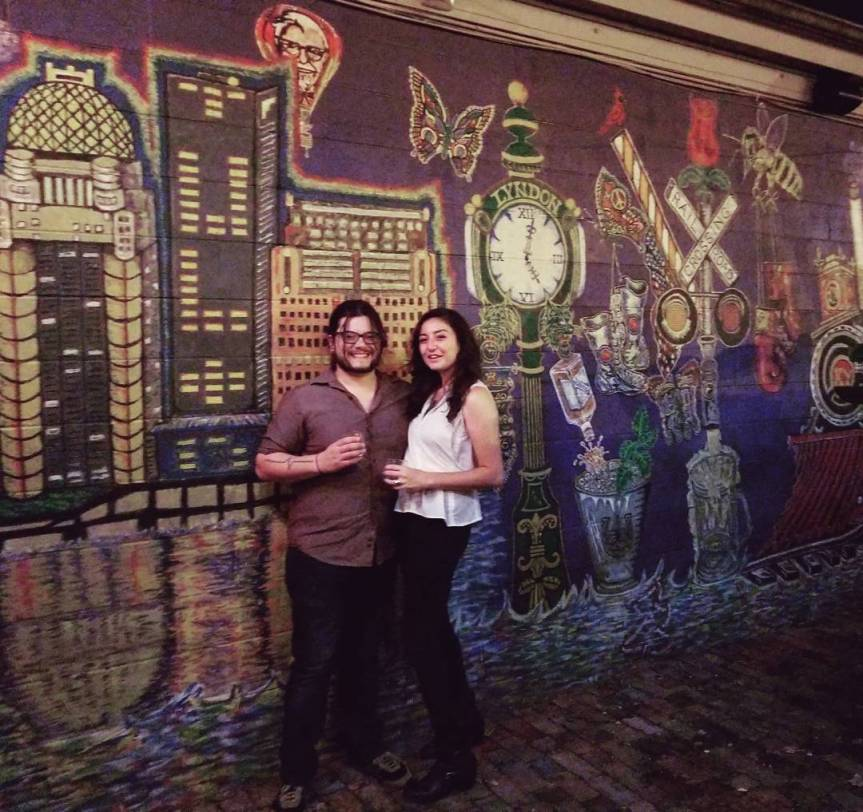 A smiling couple in front of a mural depicting landmarks of Louisville, Kentucky