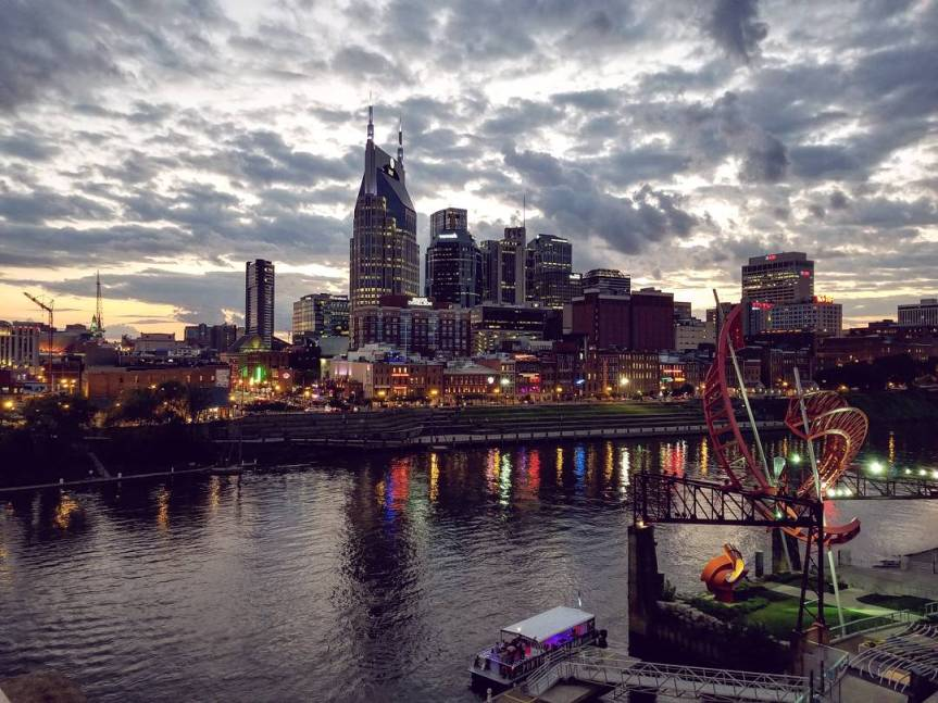 The Nashville skyline at sunset with the Cumberland River in the foreground
