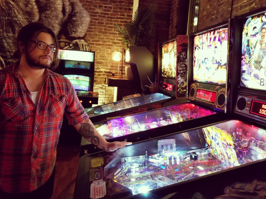 A man standing over a series of pinball tables at Headquarters in Nashville Tennessee