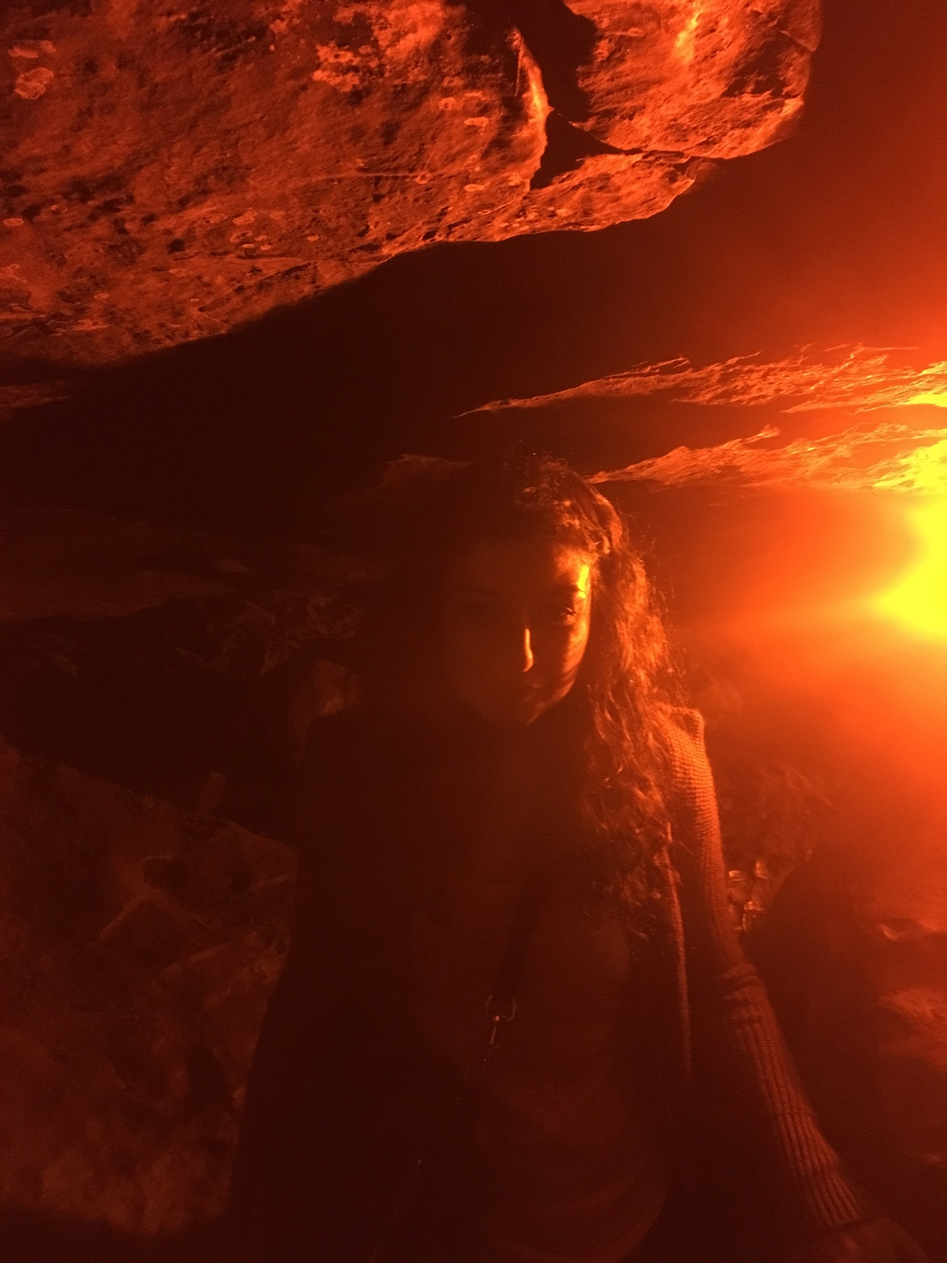 A smiling woman walking through Fat Man's Misery in the Mammoth Cave National Park