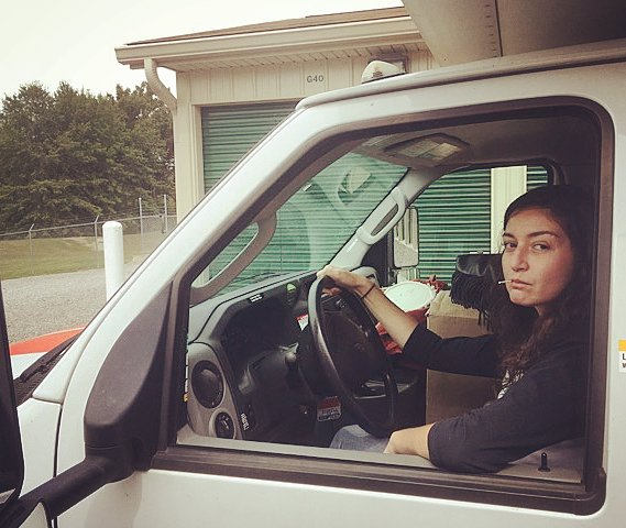 An attractive and defiant woman driving a truck.