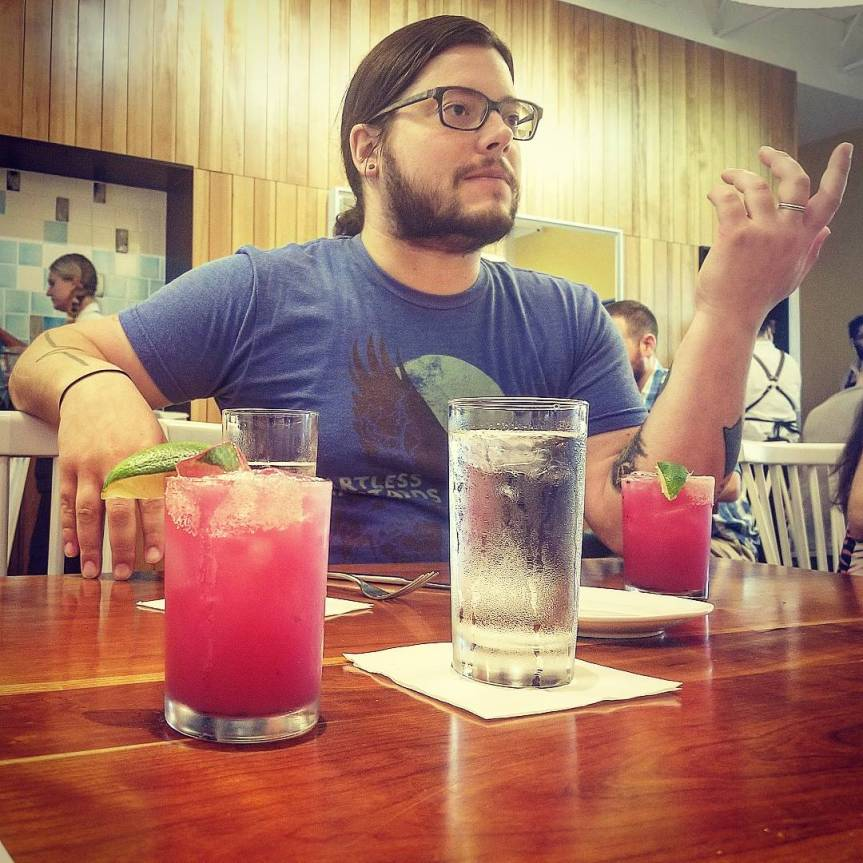 J flanked by pink dragonfruit margaritas and conversing at brunch at Picnik in Austin, Texas
