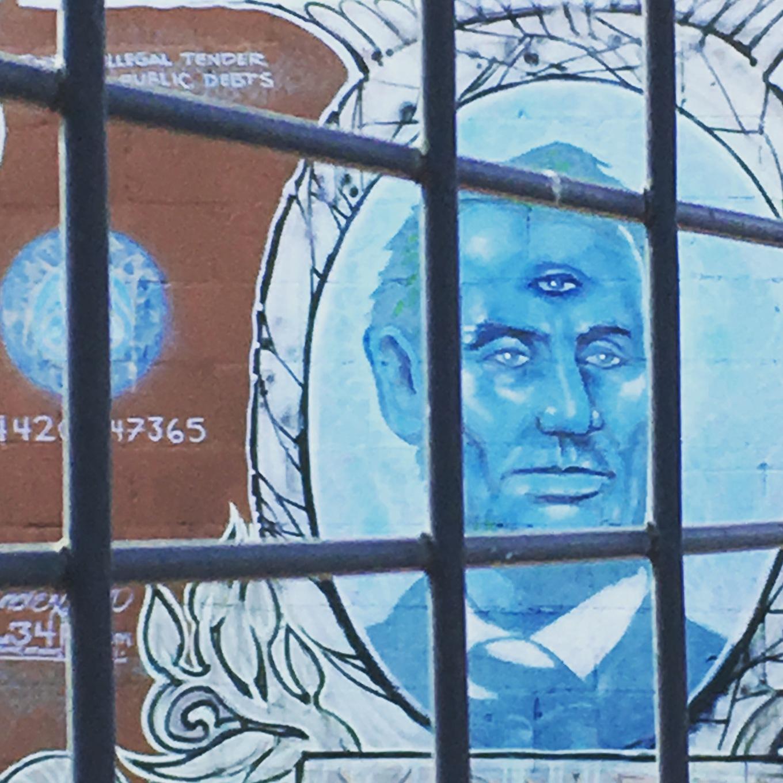 Graffiti of three-eyed Abraham Lincoln on dollar bill, on wall of Dallas, Texas graffiti park