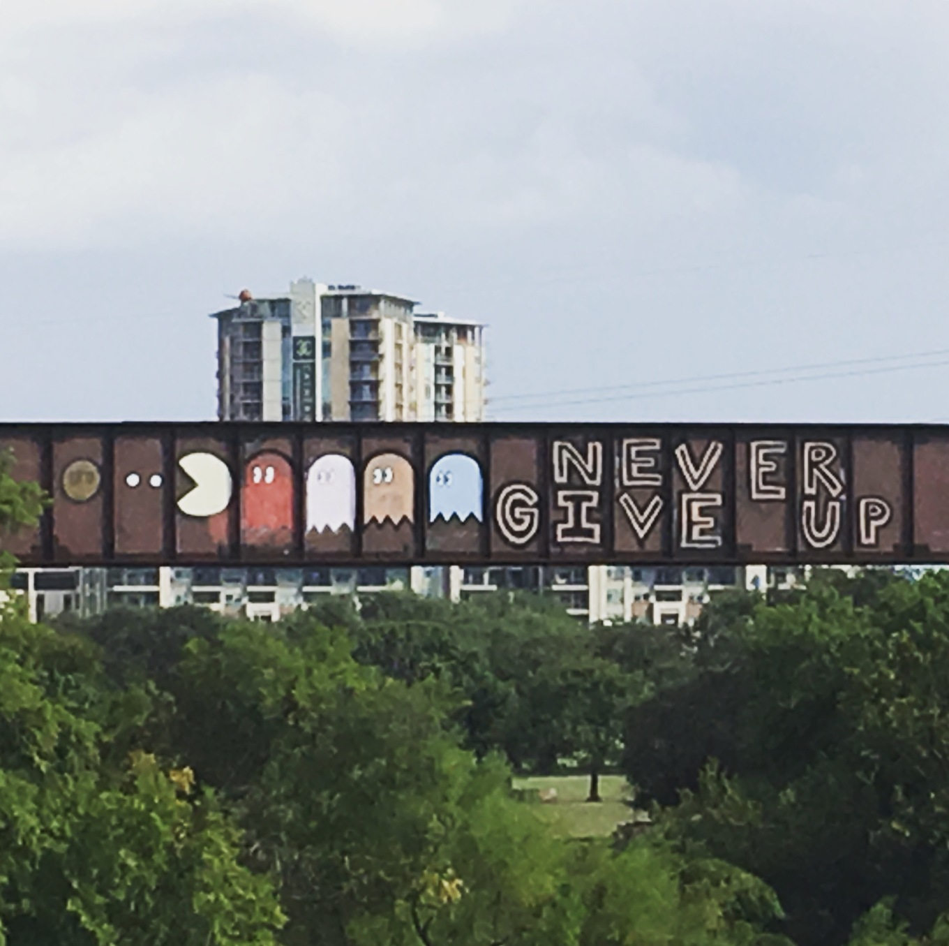 Graffiti of Pac-Man being chased by ghosts on bridge over Lady Bird Lake in Austin, Texas