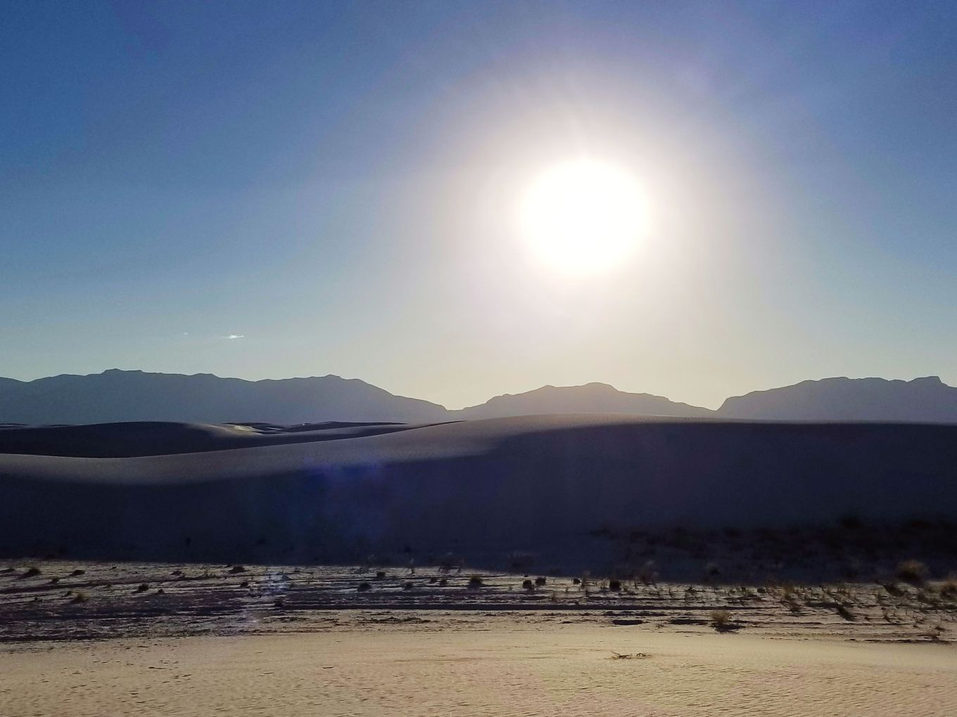 Midday sun silhouetting San Andres Mountains at White Sands National Monument