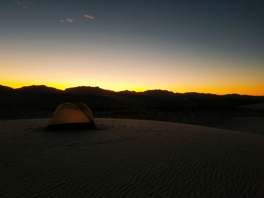 A tent set up atop a dune at sunset, the San Andres Mountains silhouetted in the background, at White Sands National Monument