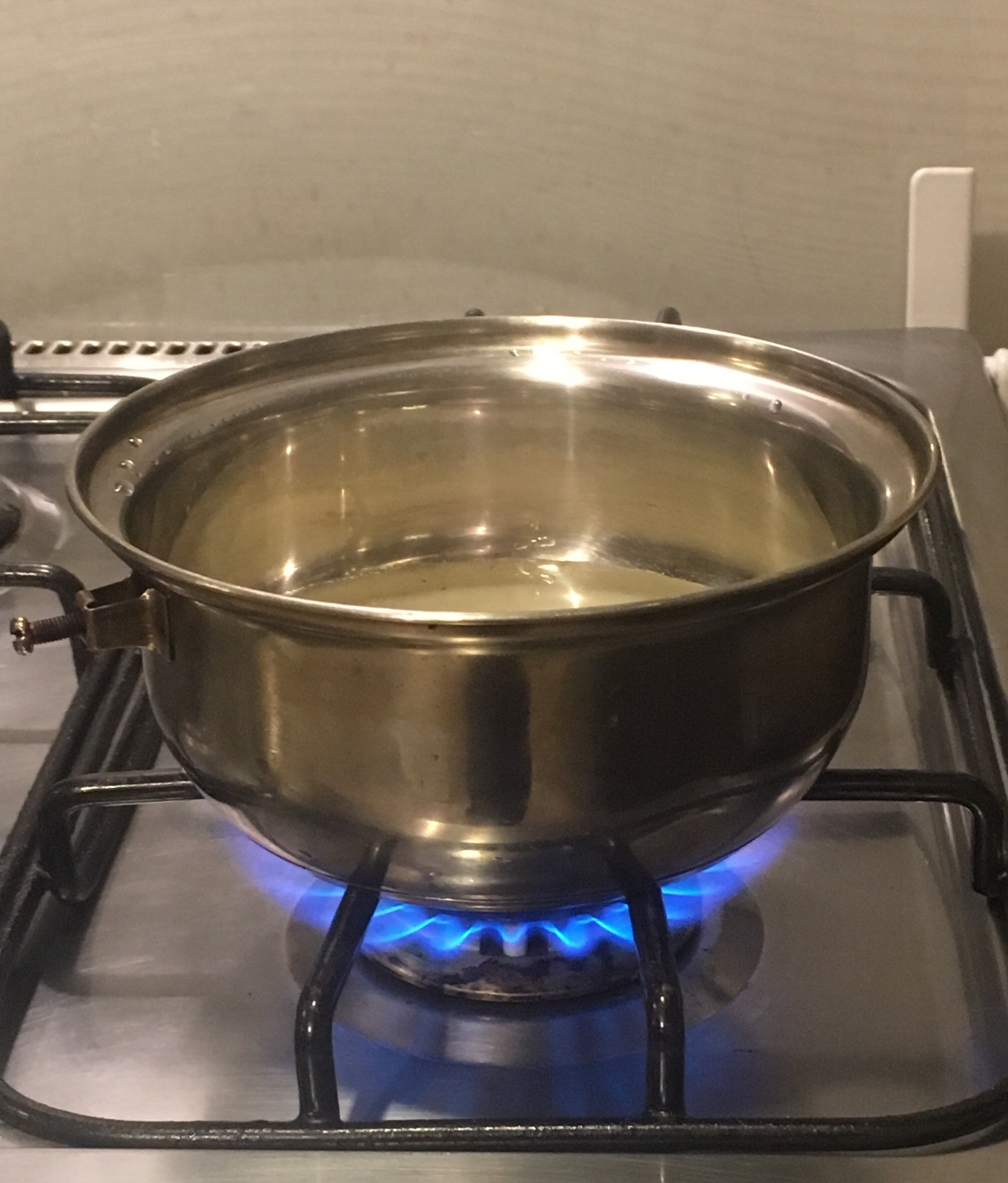 A pot over a burner containing sugar and water.