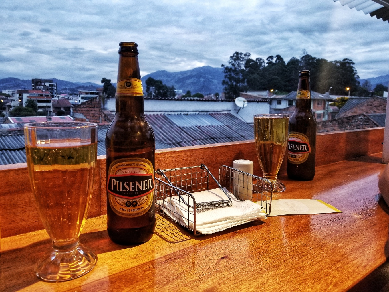 Two large bottles of Pilsener Beer in the foreground of the Andes Mountains