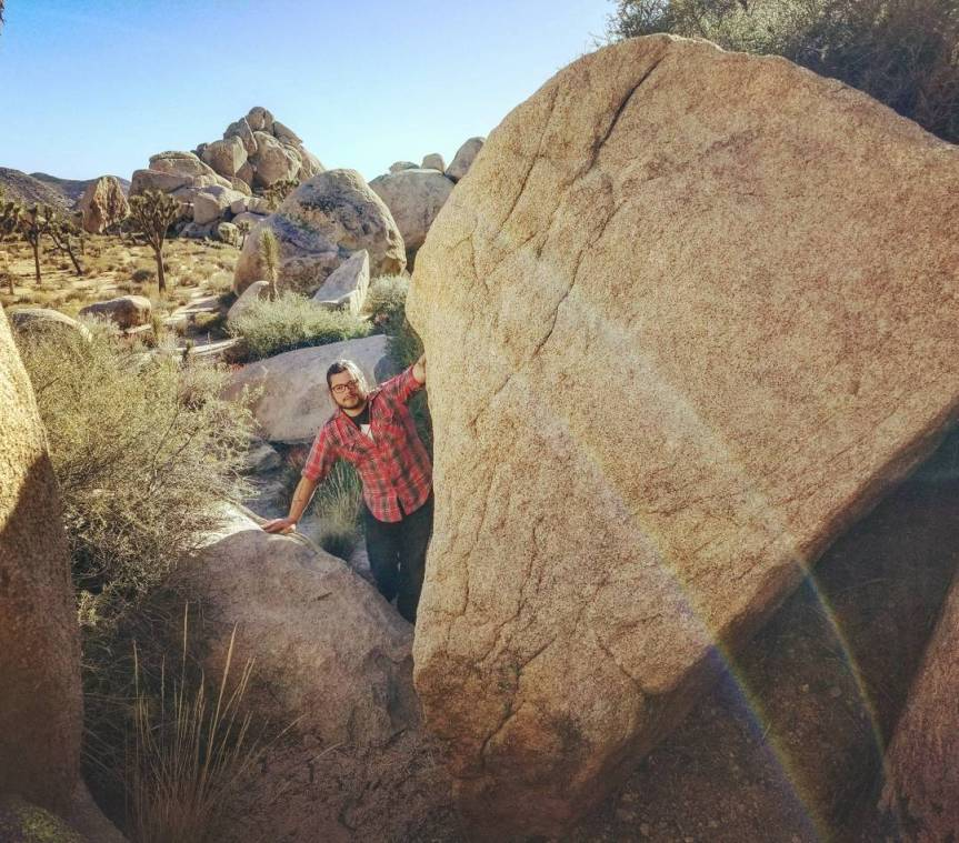 A silly man in a red flannel shirt standing amid rocks at Joshua Tree National Park