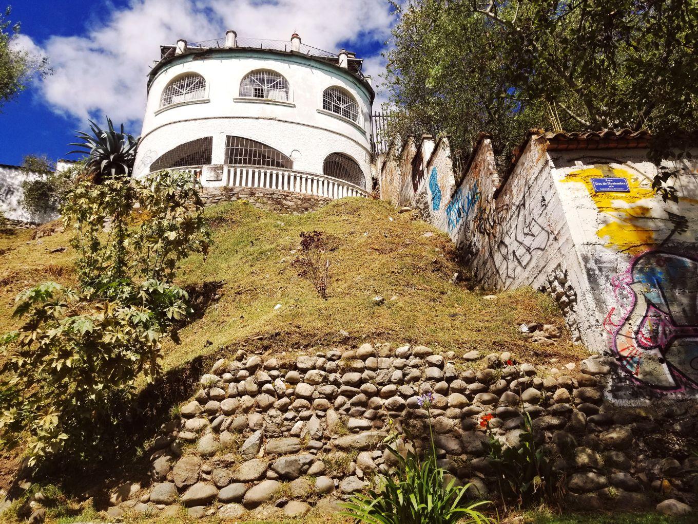 An elegant home juxtaposed by graffiti along Rio Tomebamba